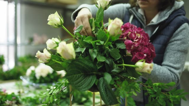 Busy woman florist working in flower workshop