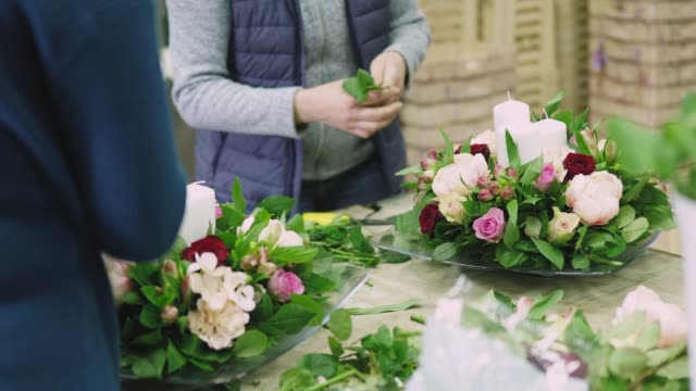 busy women working in flower workshop on arranging flowers - flower arrangement stock videos and b-roll footage