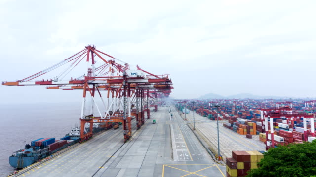 vídeos de stock e filmes b-roll de ocupado a trabalhar guindaste carregar os recipientes de camião no porto de timelapse. - contentor de carga