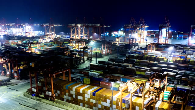 busy working crane loading containers in illuminated harbor