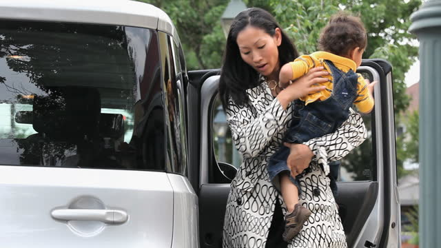 busy working mother getting child out of car - working mother stock videos & royalty-free footage