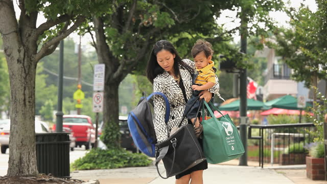 busy working mother holding child, groceries, briefcase and bag looking for car keys - working mother stock videos & royalty-free footage