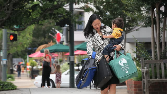 vidéos et rushes de busy working mother holding child, groceries, briefcase and bag looking for car keys - carrying