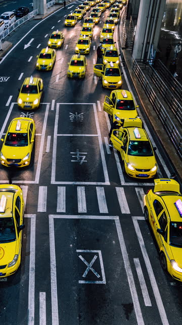 t/l pan busy yellow taxi queues at the exit of airport at night - yellow taxi stock videos & royalty-free footage