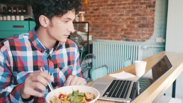 stockvideo's en b-roll-footage met drukke jongeman met laptop in de koffieshop. - freelancer