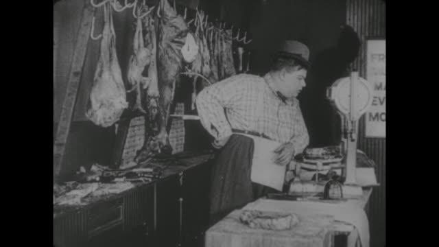 stockvideo's en b-roll-footage met 1917 butcher boy (fatty arbuckle) mis-weighs meat as he leans on scale - gewicht meeteenheid