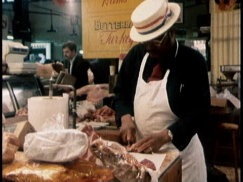 stockvideo's en b-roll-footage met 1978 ms butcher chopping meat / united states - kruidenier