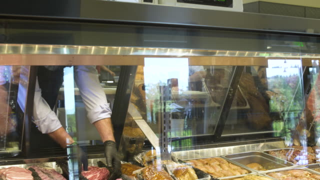 butcher putting meat on a scale - präsentation hinter glas stock-videos und b-roll-filmmaterial