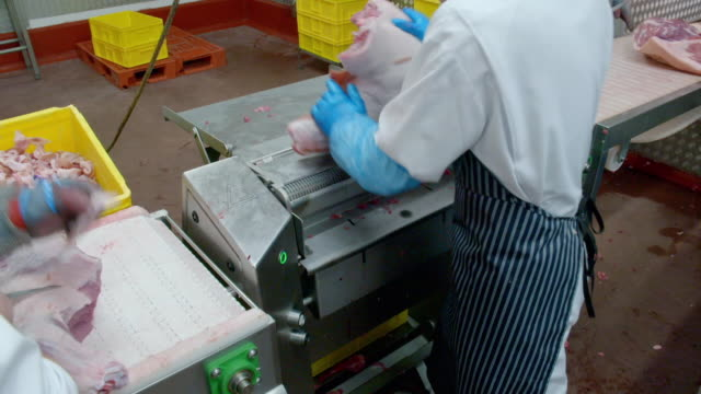 butcher removes skin from pork shoulder - tray stock videos & royalty-free footage