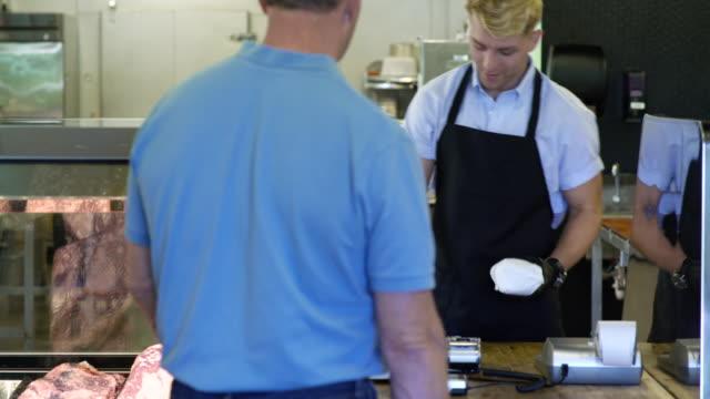 butcher serving a mature man in a butcher shop - skåp med glasdörrar bildbanksvideor och videomaterial från bakom kulisserna