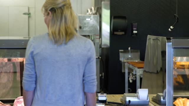 butcher serving a mature woman in a butcher shop - präsentation hinter glas stock-videos und b-roll-filmmaterial