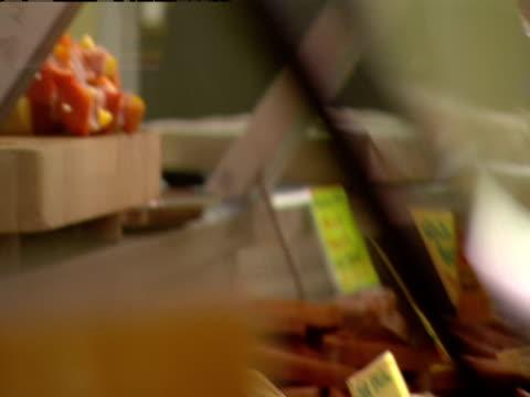 a butcher skewers meat behind a display case. - 陳列ケース点の映像素材/bロール