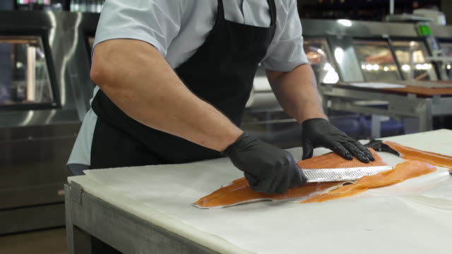 Butcher slicing a fresh fish