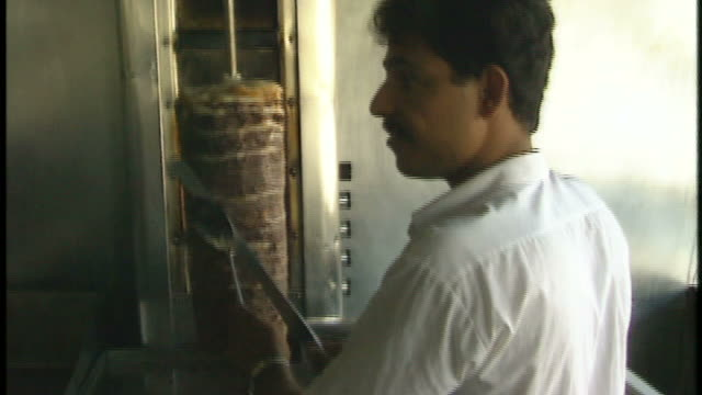 TD Butcher slicing meat in commercial kitchen where chefs are working / Baghdad Iraq