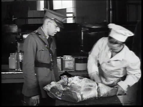 stockvideo's en b-roll-footage met 1934 montage butcher working in kitchen as uniformed man watches / united states - grote depressie nieuwsevenement