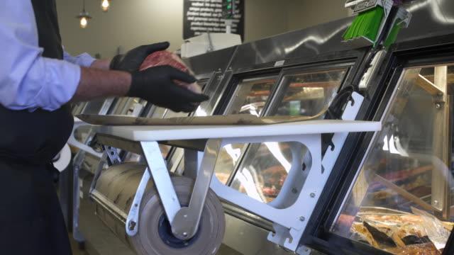butcher wrapping meat in paper - skåp med glasdörrar bildbanksvideor och videomaterial från bakom kulisserna
