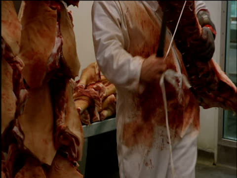 Butchers cut meat from hanging beef quarters at Smithfield Market
