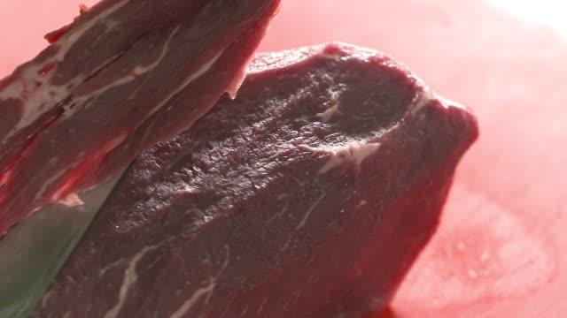vidéos et rushes de butcher's hands cutting meat with a knife - couteau de cuisine