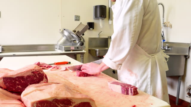 MS ZO Butchers in butcher shop preparing meat for customers