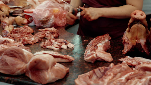 butcher's row. saleswoman sharpening knives to chop meat up - meat chop stock videos and b-roll footage