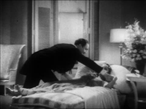 stockvideo's en b-roll-footage met b/w 1936 butler picking up sleeping woman from bed / feature - huishoudelijke dienstverlening