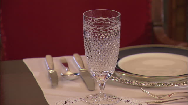 ms butler placing three glasses at place setting on table/ slovenia - place setting stock videos & royalty-free footage