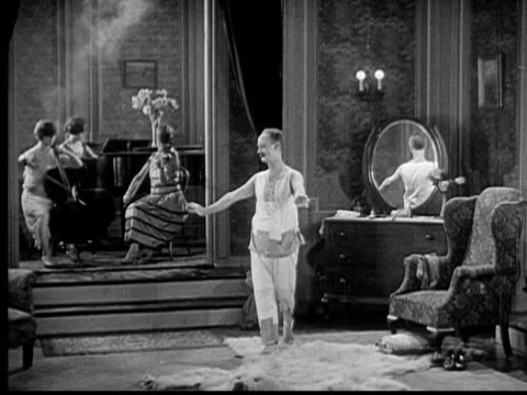 1926 b/w ws butler removing robe from man (ben turpin) who stretches and dances around room while women play musical instruments / usa - anno 1926 video stock e b–roll