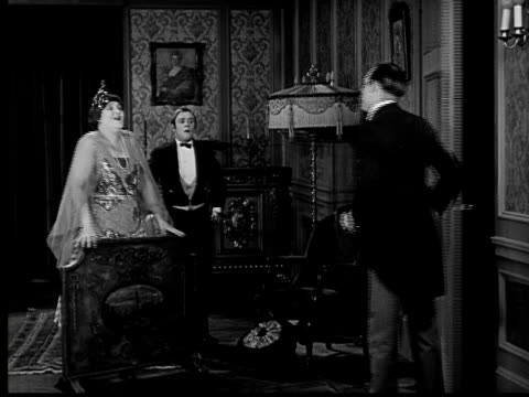 1924 b&w ms butler scrambling to cover up woman's bloomers sticking out from under torn dress before guest enters room  - respect stock videos & royalty-free footage