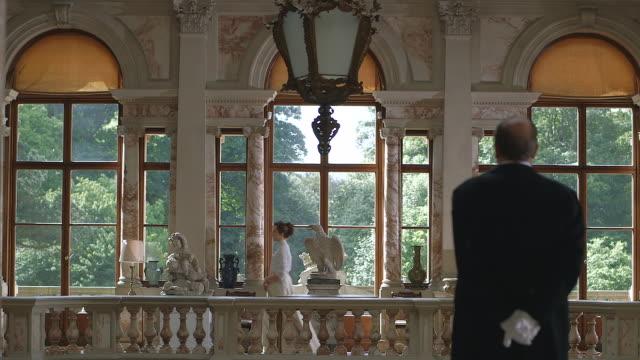 ms butler watching consuelo vanderbilt walking down hallway / united kingdom - collaboratore domestico video stock e b–roll