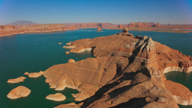 aerial butte rising above lake powell lit by the sun - lake powell stock videos & royalty-free footage