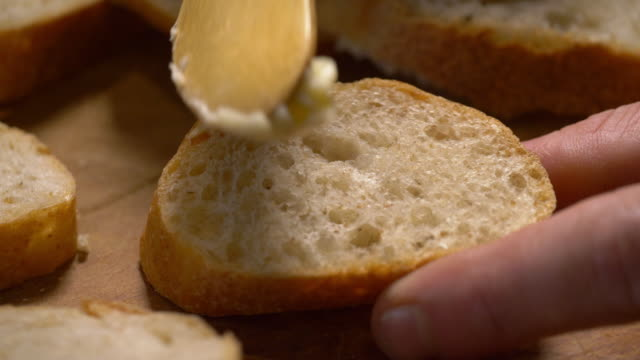 butter being spread on fresh bread on a wooden cutting board. - positive emotion stock videos & royalty-free footage