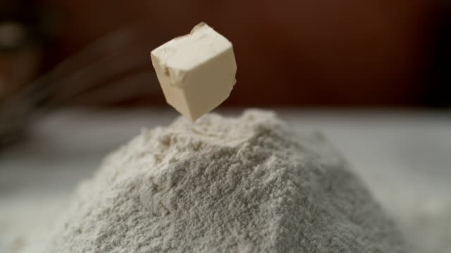 butter falling into heap of flour. super slow motion - butter stock videos and b-roll footage