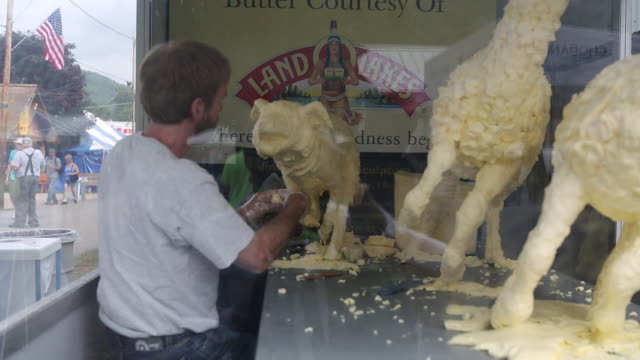 butter sculptor working with his medium at the delaware county fair. - fairground stall stock videos & royalty-free footage
