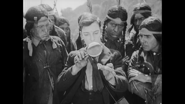 1922 Butterfly hunter (Buster Keaton) catches butterfly on top American Indian chief's head