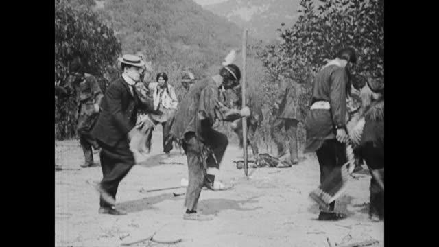 vídeos de stock e filmes b-roll de 1922 butterfly hunter (buster keaton) gets into american indian war dance - dança da guerra