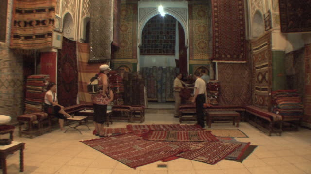 ws buyers looking at rugs in large rug emporium, fez, morocco - ラグ点の映像素材/bロール