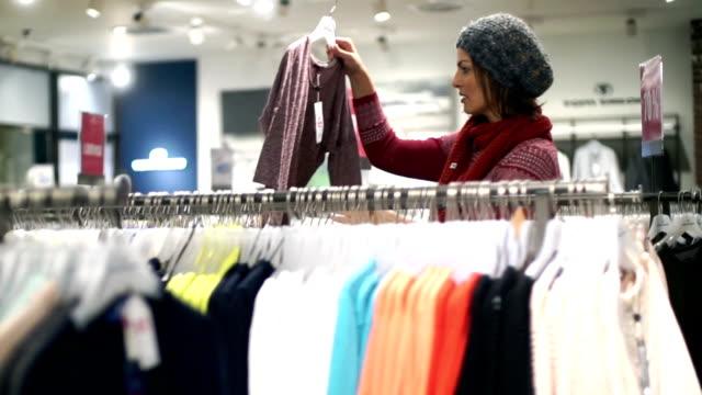 stockvideo's en b-roll-footage met kopen kleren in de detailhandel slaan spiegel. - kledinghanger