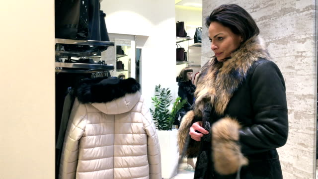 vídeos de stock, filmes e b-roll de comprar roupas na loja de varejo. - casaco