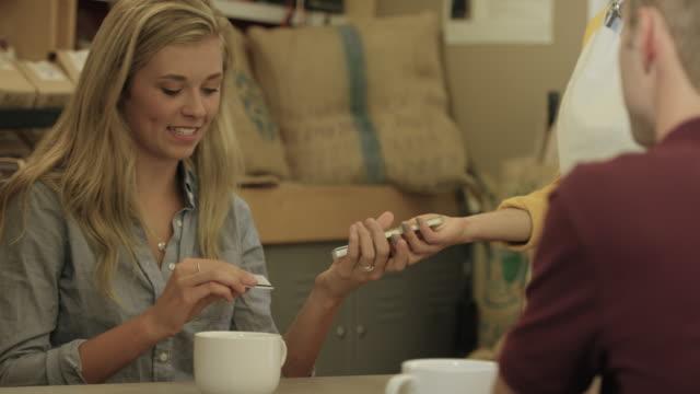 stockvideo's en b-roll-footage met het kopen van koffie met behulp van een mobiele telefoon en credit card - natuurlijk haar
