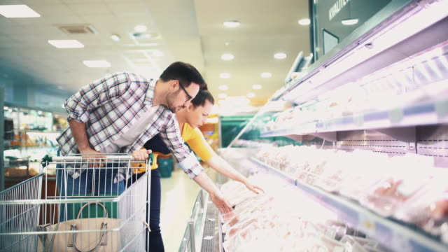 vídeos de stock e filmes b-roll de buying food in supermarket - fazer compras
