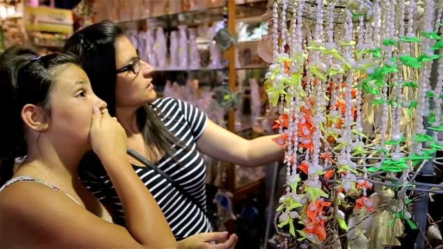 vídeos de stock e filmes b-roll de buying souvenirs on summer vacation is always fun - camisas