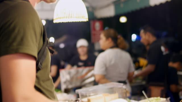 stockvideo's en b-roll-footage met street food naar avondmarkt kopen - marktkoopman