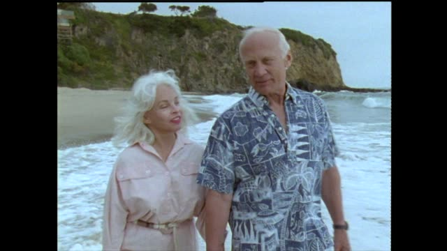 buzz and lois aldrin walk along a beach and talk about how they met and how they feel about one another - candid stock videos & royalty-free footage