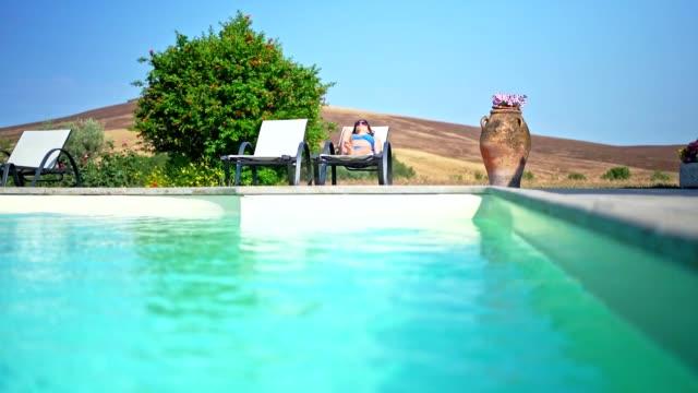 vídeos de stock e filmes b-roll de by the pool - biquíni