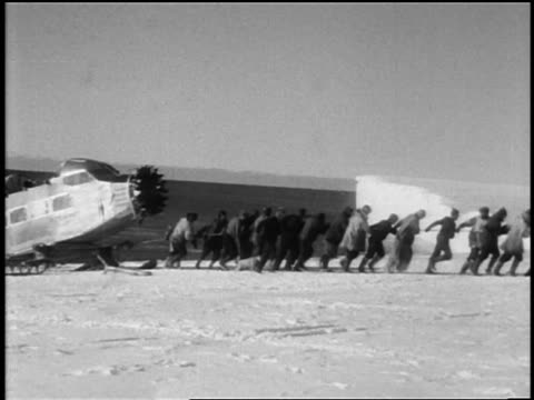 byrd's crew pulling part of airplane for antarctic expedition on skis / documentary - 1920 1929 stock videos & royalty-free footage