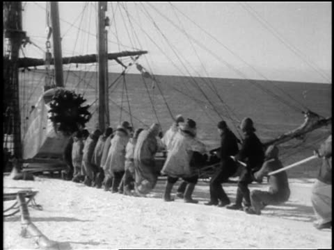 byrd's crew pulling part of airplane for antarctic expedition onto land from ship - anno 1928 video stock e b–roll
