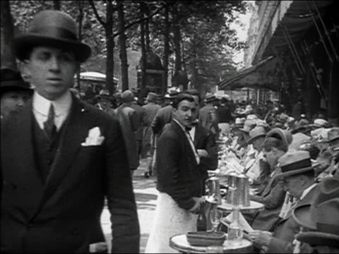 vídeos de stock, filmes e b-roll de ca. 1929 - 1930 b/w ms pedestrians walking past waiters and customers at outdoor cafe / paris, france - 1920 1929