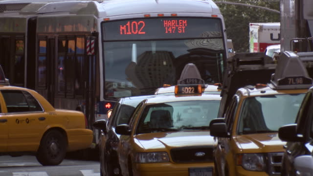 cab and a mta bus navigate traffic on a busy street in manhattan. - ora di punta video stock e b–roll