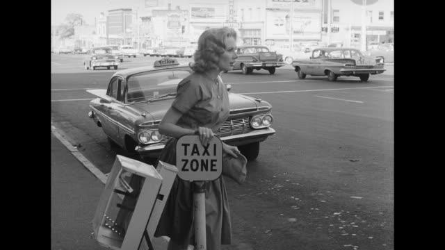 vidéos et rushes de 1962 a cab pulls away as a woman approaches it - invisible