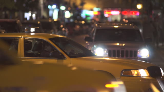 A cab sits profile while cars whiz by.  A women gets into the cab and they drive off.